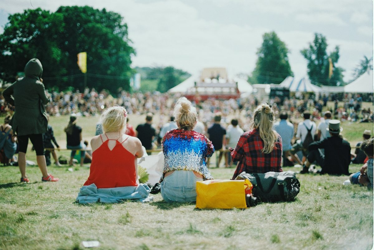 A group of people on grass field on a sunny day at a festival.