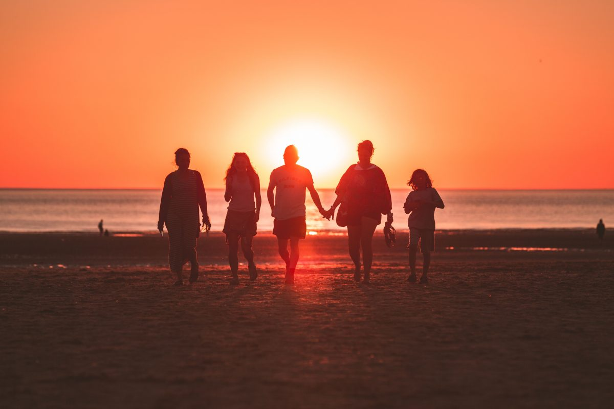 Family and Friends walking on the beach at sunset.