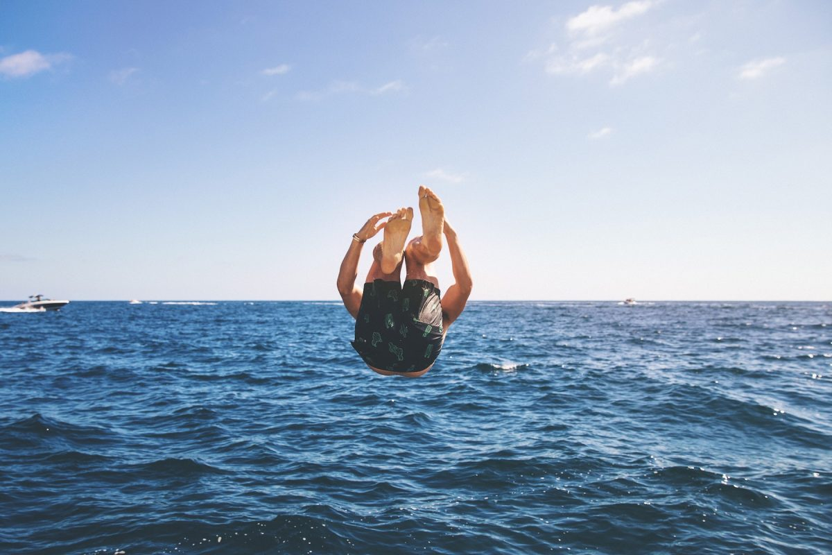 A guy jumping into the sea.