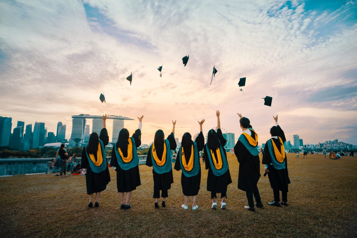A group of people graduating and throwing their caps in the air.
